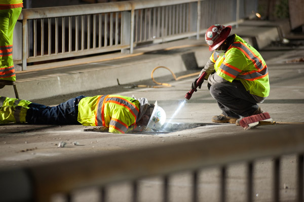 A worker inspects under the bridge deck of the northbound on-ramp from westbound Wilshire. Another worker shines a flashlight into the abyss.