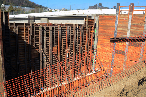Temporary supports push against the eastside abutment. The completed north side of Skirball Dr Bridge can be seen above the abutment.