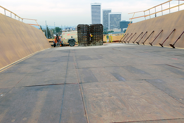 Looking south, this photo shows the plywood false work which will form the bottom of the concrete bridge deck. To make it easier to strip the plywood from the poured concrete, the plywood has been coa