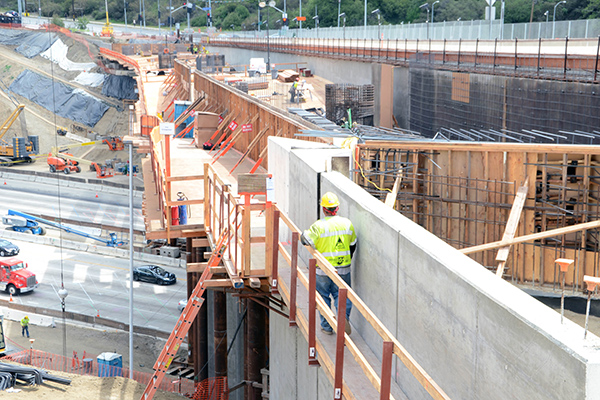 A worker passes the site of the future west side abutment (abutment 1) of the 608-foot-long bridge.