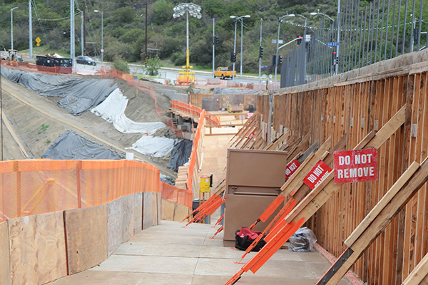 Behind this supporting wall, workers lay rebar for a future concrete pour. Mulholland Dr can be seen in the background.