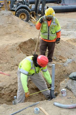 Workers measure a piece of electrical conduit for traffic signals for the  reconfigured Moraga Dr ramps.