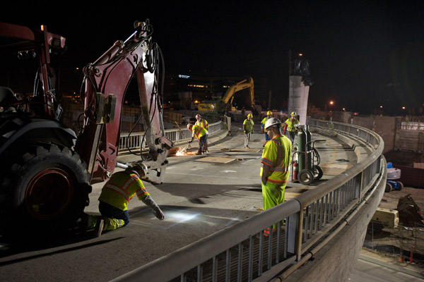 A worker marks the location of the next hole punched in the bridge deck. In the background another worker cuts rebar with an acetylene torch. The photographer was facing southwest.