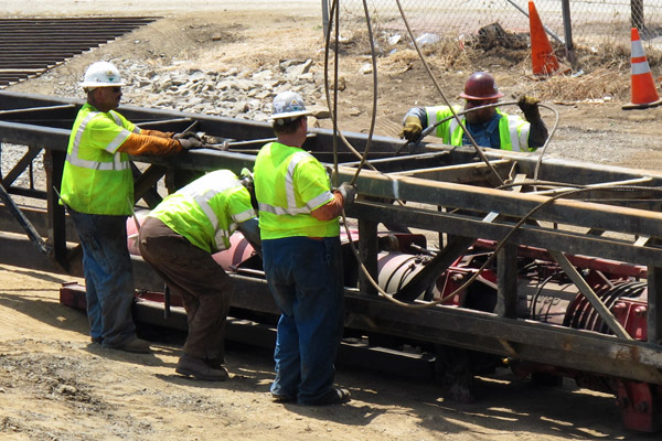 <p>Workers assemble the pile-driving hammer in the lead (its housing) to prepare for pile-driving operations.</p>