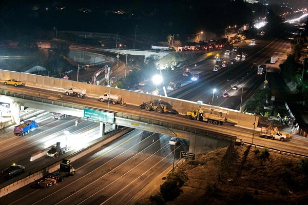 <p>Looking southeast, this views shows two water trucks on Sunset Bridge and the closure of the northbound lanes. The section of the bridge over the northbound I-405 was demolished first. Demolition of the span over southbound lanes began Sunday, July 25. All demolition occurs at night to limit restrictions on the highway&rsquo;s capacity.</p>