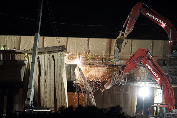 Behind sound blankets, two hoe rams, resembling giant mechanical elephants, pound away at the span over the northbound I-405. Soil was placed below the bridge to catch falling pieces of concrete.