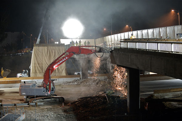<p>Lit by powerful work lamps, a hoe ram knocks away rebar and concrete. The first phase of Sunset Bridge demolition ended with removing the center columns on Thursday, July 29.</p>