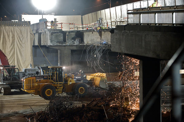 <p>Under a nest of steel rebar, a loader scoops up fallen concrete. Soil was spread under the bridge to protect the freeway surface from chunks of concrete loosened by the hoe rams. Reconstructing the south side of Sunset Bridge will take approximately 10 months.</p>
