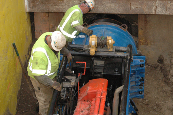 <p>Workers use a diesel engine mounted on a short track to extract another auger from the new tunnel under Wilshire Bl.</p>