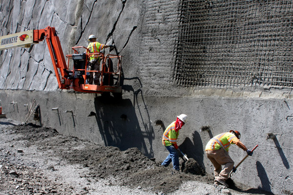 While one worker scores the fresh concrete to give it a rock-like appearance, two workers shovel fallen concrete away from the bottom of the wall. This fallen concrete failed to stick to the wall's wi
