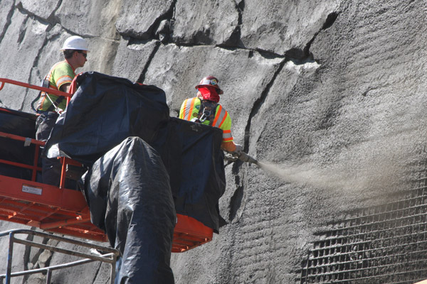 <p>Here is a closer view of workers spraying the shotcrete into the wire mesh surface. Giant nails keep the wall in place by securing its steel and concrete fa&ccedil;ade.</p>