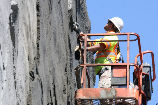 <p>Fifty feet above the I-405 a worker scores the concrete. Uncovered wire mesh can be seen behind and below him. The wall will eventually be stained to more closely resemble rock.</p>