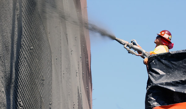 "<p>High above the southbound Getty Center   Dr on-ramp, a worker sprays ""shotcrete"" on the wire mesh surface of Wall 1827. The retaining wall is needed to contain the hillside. This is needed because the freeway and on-ramp will be moving slightly to the west here as the southbound lanes are widened to a standard of 12 feet.</p>