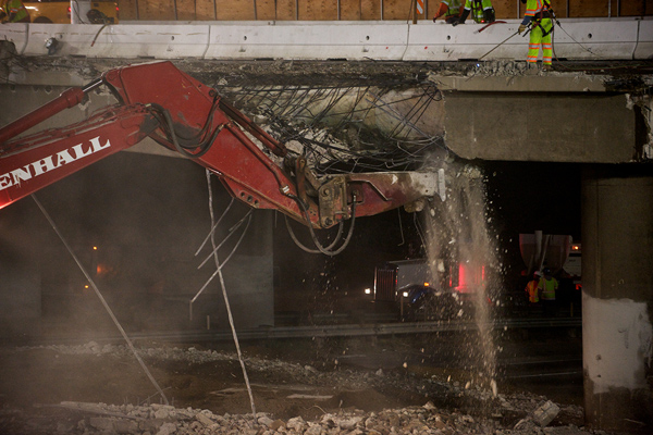 <p>Looking southeast, this photograph captures a hoe ram breaking the bridge&rsquo;s deck supports. Soil was spread under the bridge to protect the roadway from falling concrete.</p>