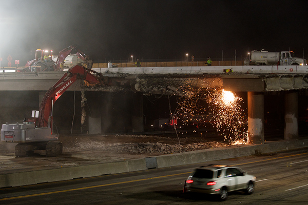 <p>After midnight, workers demolish the east section of the bridge while traffic flows on the southbound lanes.</p>