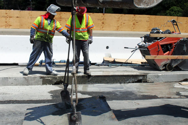 <p>Resembling a concrete brownie, the newly removed deck piece opens another work area over the water line. Water used to cool the concrete saw and control dust has soaked the deck piece.</p>
