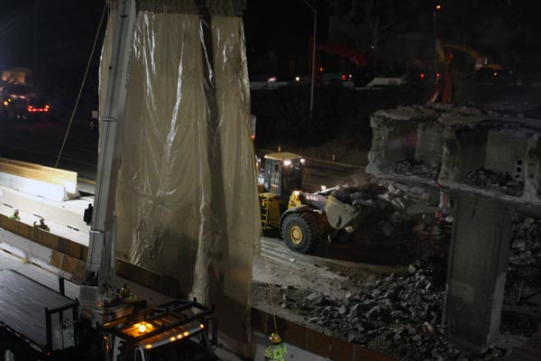 While a sound blanket rises  to the left, fallen concrete from the demolition is scooped up from the road  surface of the southbound lanes of the I-405.