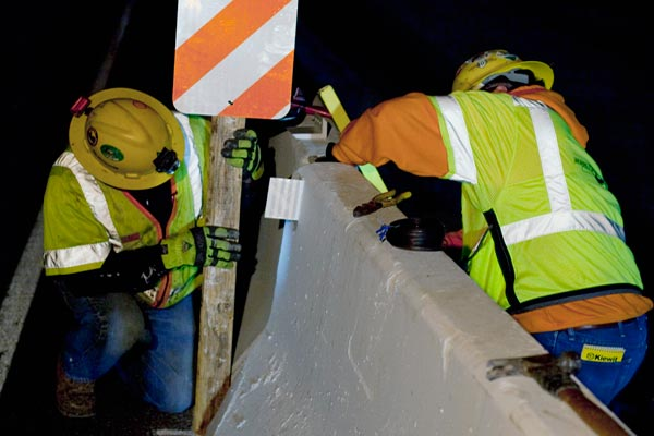 <p>Workers install a reflector, called a Type-P marker, on the traffic side of the K-Rail. The reflectors are typically used where there is a kink in the alignment of the barriers. The white and orange scheme is commonly used in construction zones.</p>
