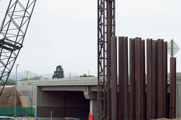 <p>A lattice boom truck crane holds the hammer housing erect. The Wilshire Bl pile driving was the first pile driving on the I-405 Sepulveda Pass Improvements Project. In the near background, Wilshire Bl carries traffic. This set of piles rest south of Wilshire Bl and west of the I-405.</p>