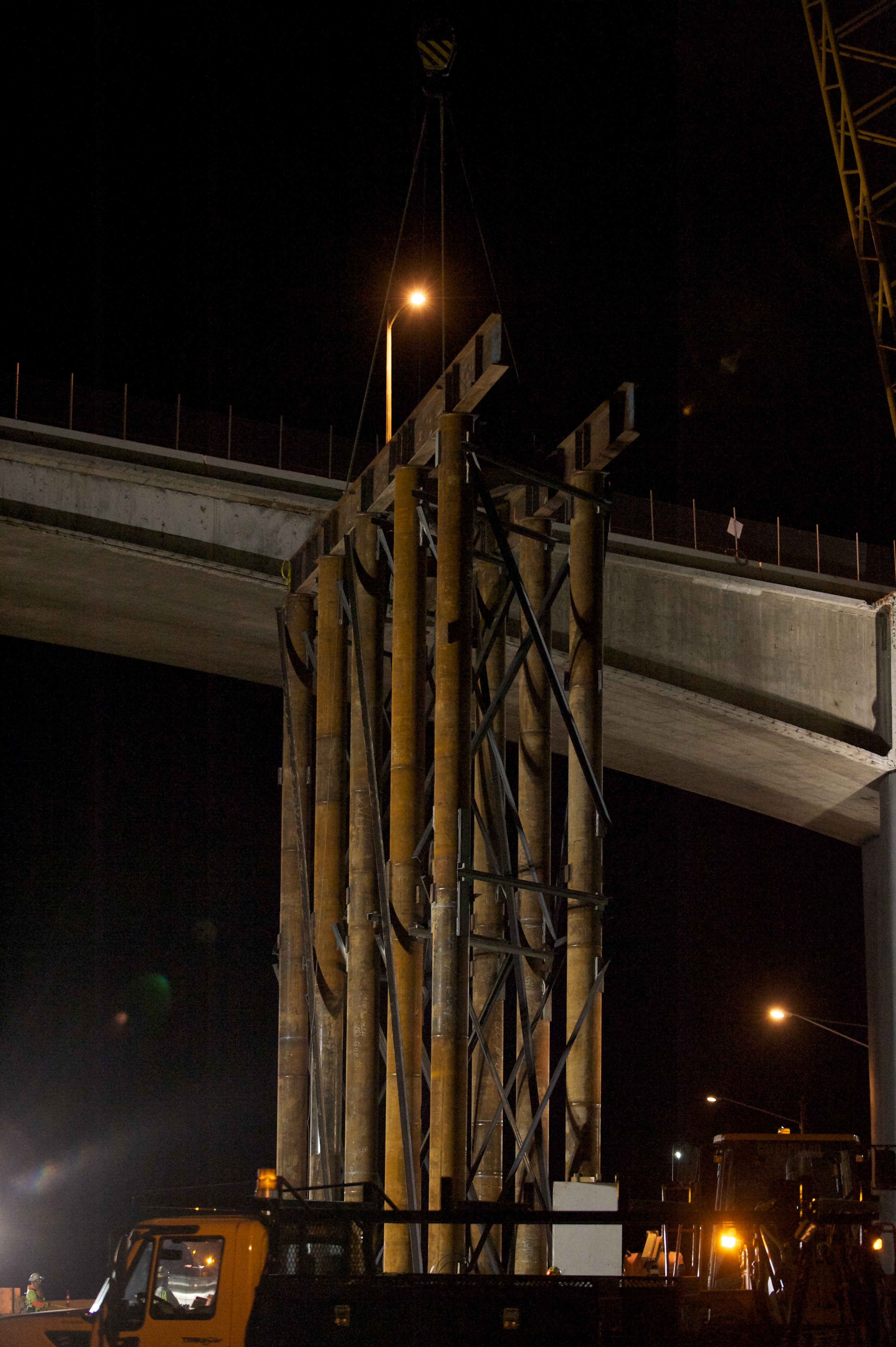 <p>Long after midnight, workers move the new center column into place.</p>